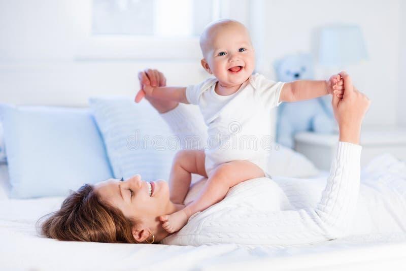 Madre y bebé en una cama blanca imagen de archivo