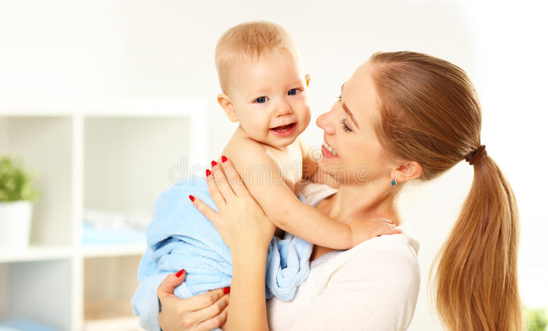 Madre y bebé felices de la familia en una toalla azul después de bañar fotos de archivo