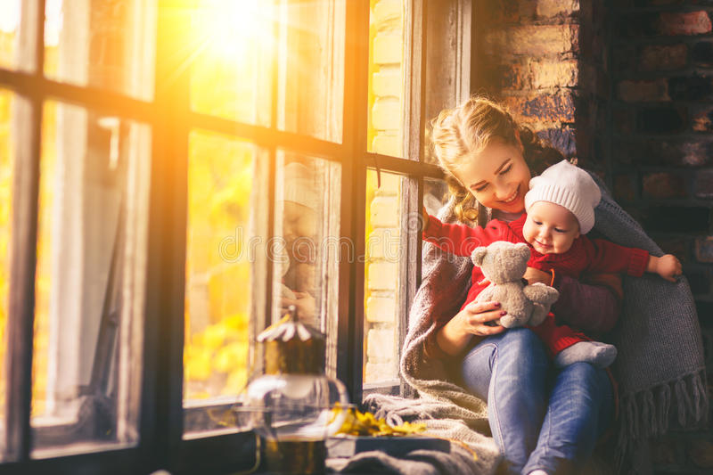 Madre y bebé felices de la familia en ventana del otoño imagen de archivo libre de regalías