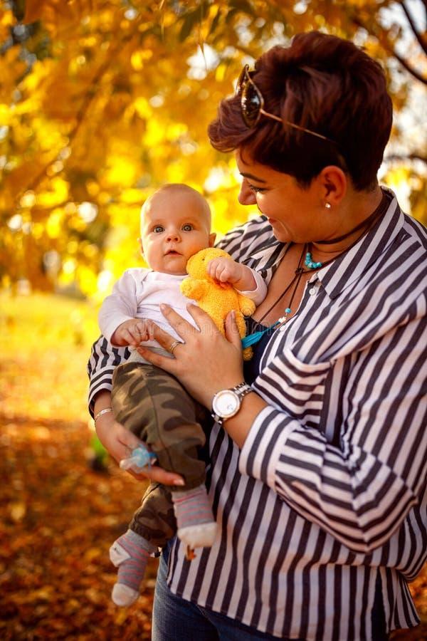 Madre y bebé jovenes en parque del otoño foto de archivo libre de regalías