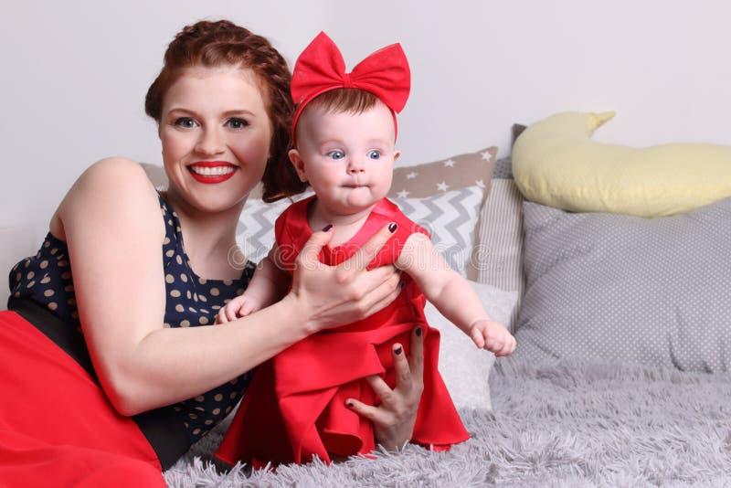 Madre y bebé jovenes en vestido rojo en cama fotografía de archivo