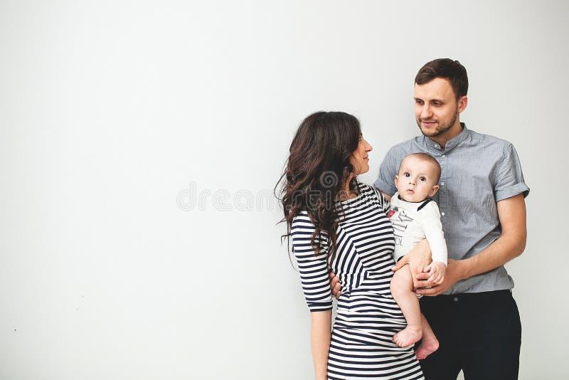 Madre y bebé jovenes felices del padre sobre el fondo blanco imagenes de archivo