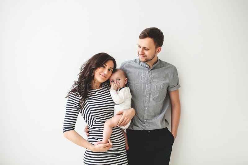 Madre y bebé jovenes felices del padre sobre el fondo blanco imagen de archivo