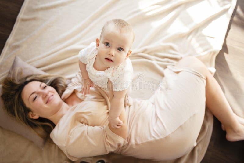 Madre y bebé que abrazan y que juegan la mentira en cama dentro Visión superior imagen de archivo libre de regalías