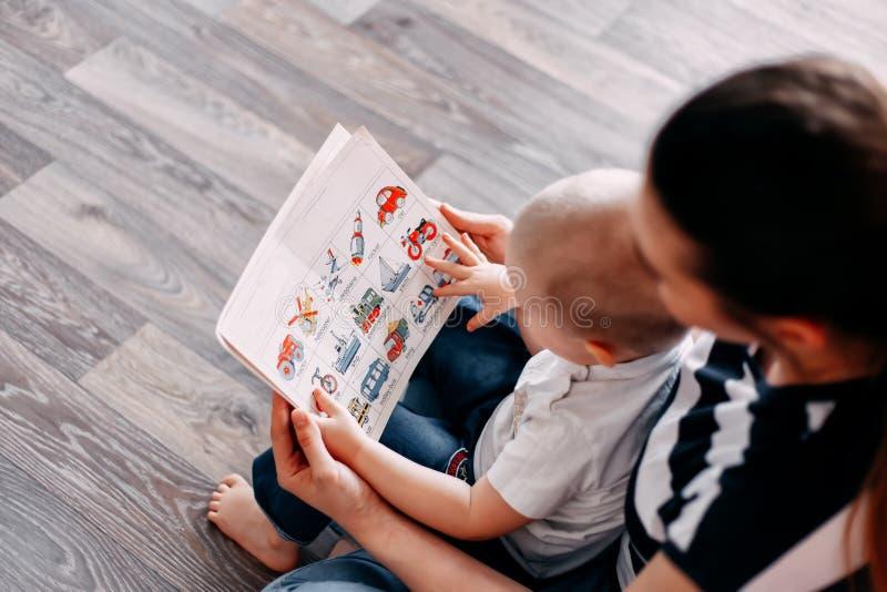 Madre y bebé que aprenden el libro de enseñanza imagen de archivo libre de regalías
