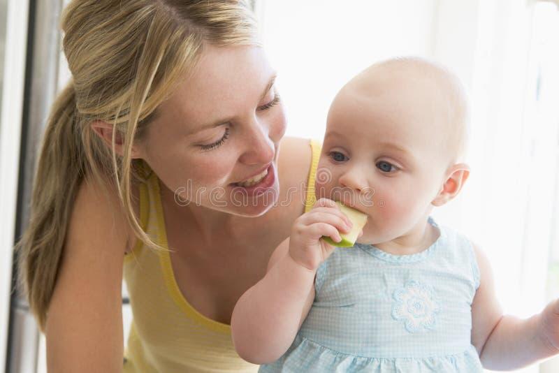 Madre y bebé que comen la manzana imágenes de archivo libres de regalías