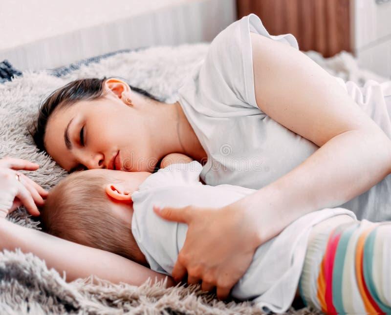 madre y bebé que duermen junto en cama imagenes de archivo