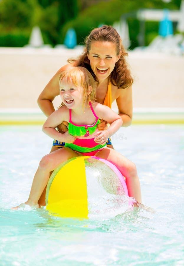 Madre y bebé que juegan con la pelota de playa en piscina fotos de archivo libres de regalías
