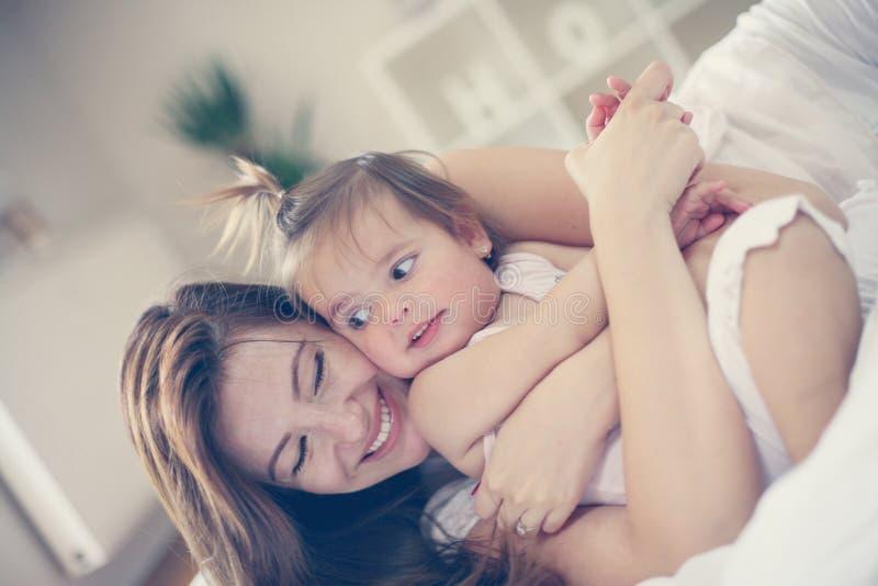 Madre y bebé que juegan en la cama foto de archivo libre de regalías