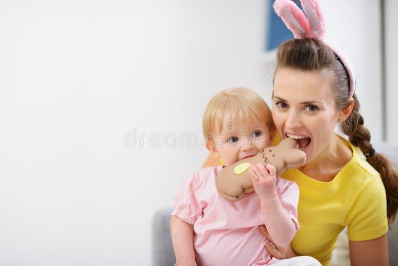 Madre y bebé que muerden la galleta del conejo de Pascua fotos de archivo libres de regalías