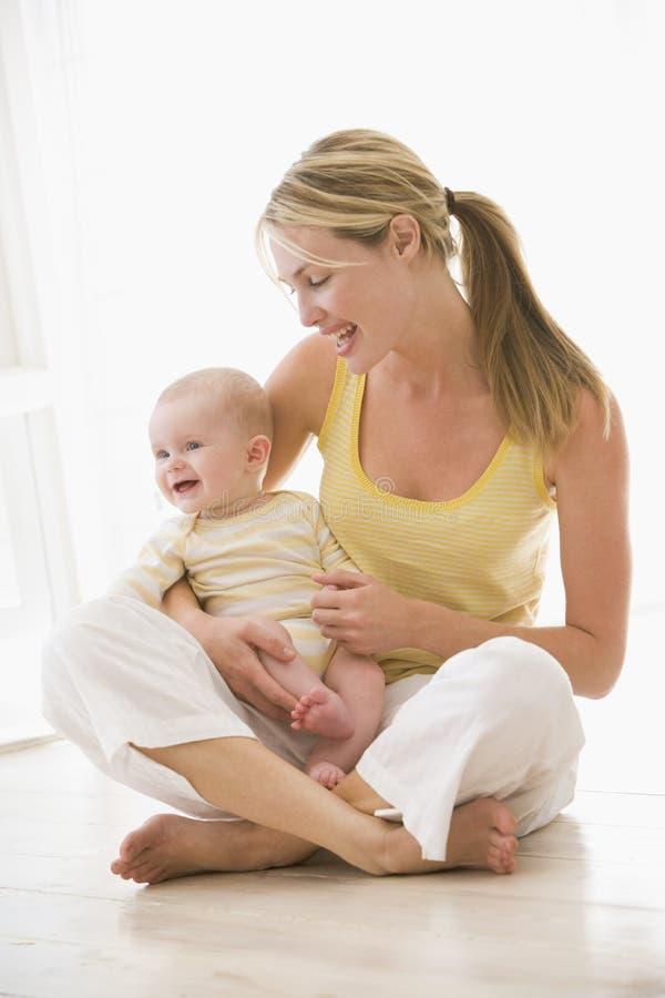 Madre y bebé que se sientan dentro foto de archivo