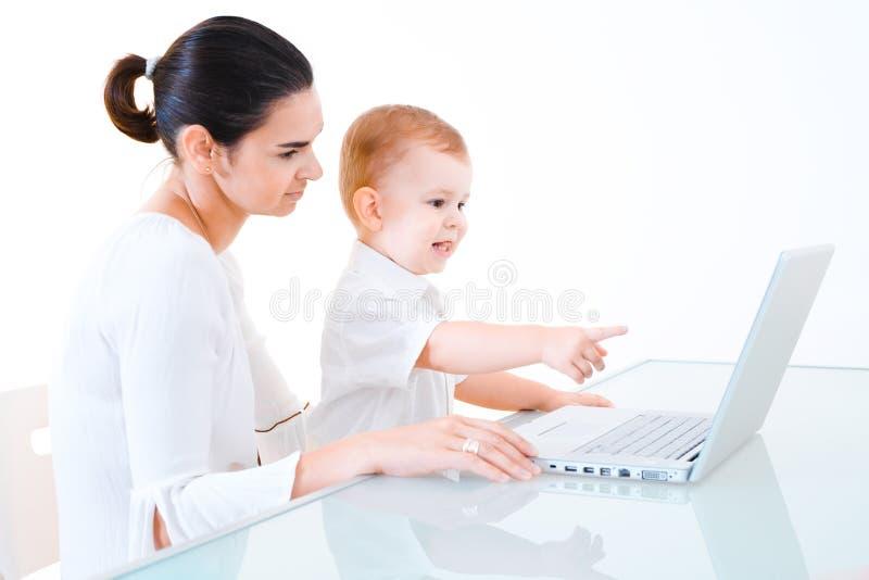 Madre y bebé que usa la computadora portátil imagen de archivo libre de regalías