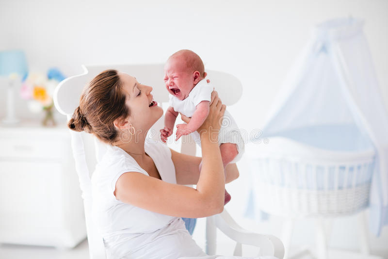 Madre y bebé recién nacido en el cuarto de niños blanco imagen de archivo libre de regalías