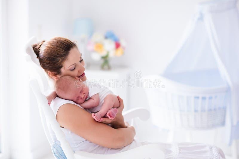 Madre y bebé recién nacido en el cuarto de niños blanco imagen de archivo