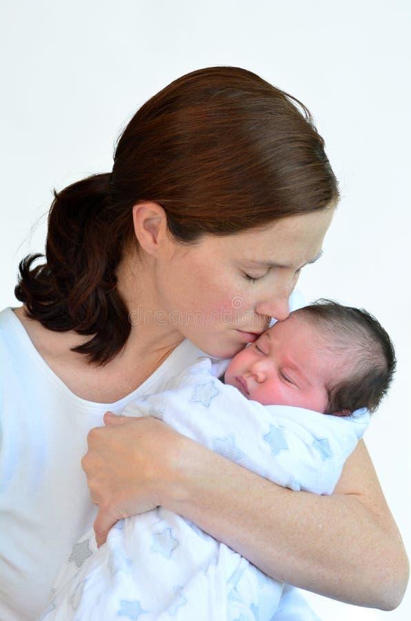 Madre y bebé recién nacido que se besan y que abrazan fotografía de archivo libre de regalías