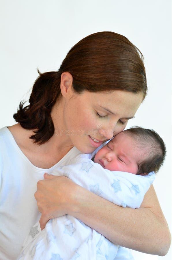 Madre y bebé recién nacido que se besan y que abrazan imagen de archivo libre de regalías