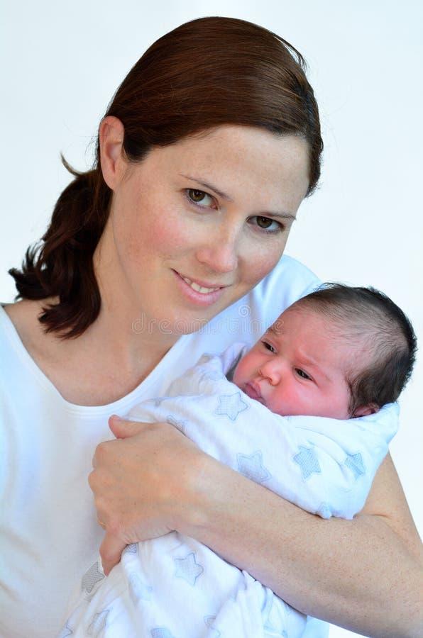 Madre y bebé recién nacido que se besan y que abrazan imagenes de archivo