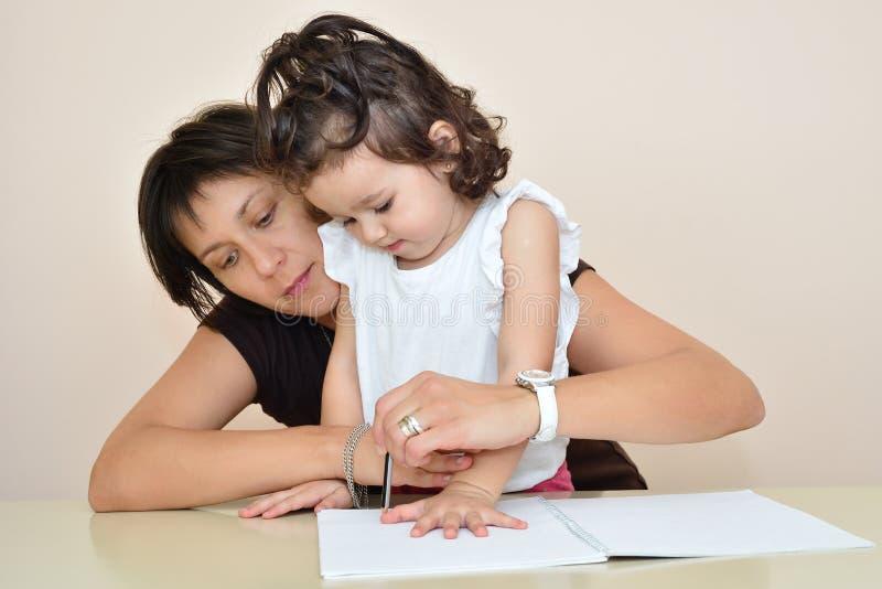 Madre y dibujo y el jugar de la hija imagenes de archivo