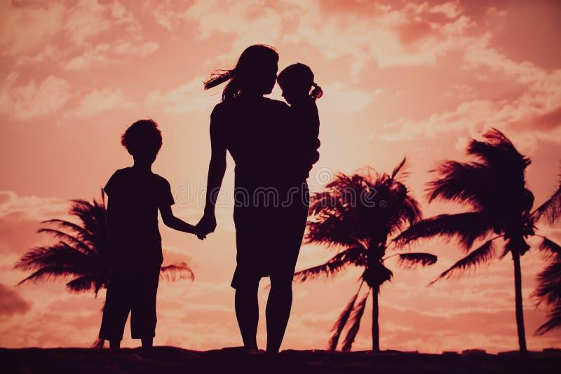 Madre y dos hijos caminando en la playa de la puesta de sol fotos de archivo
