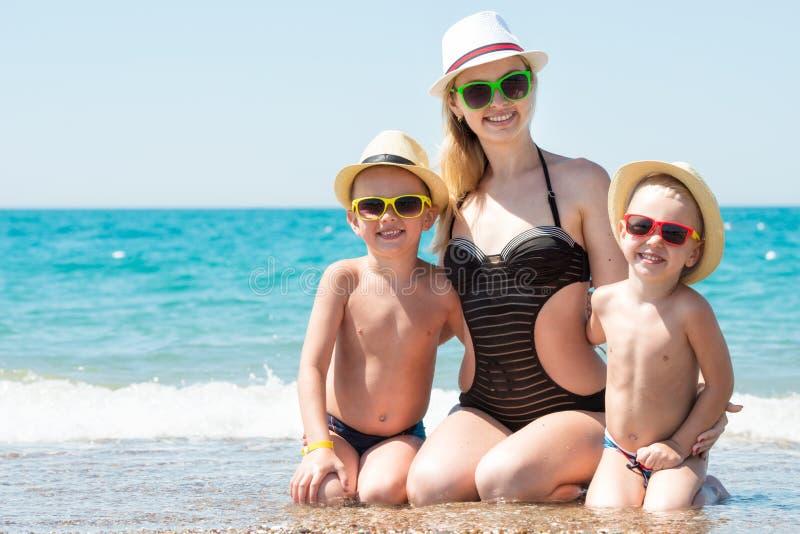 Madre y dos hijos en los sombreros que se sientan en la playa Vacaciones de familia del verano foto de archivo