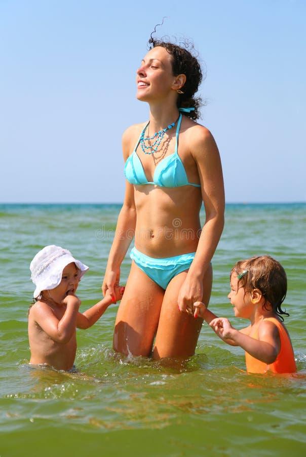 Madre y dos niños en el mar foto de archivo