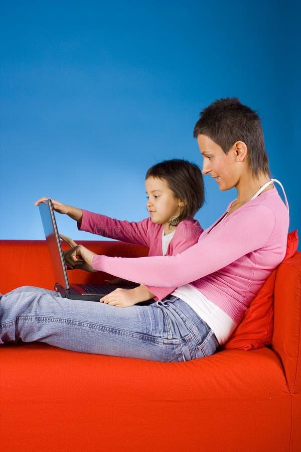 Madre y douther con la computadora portátil imagen de archivo