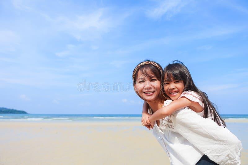 Madre y hija en la playa imagenes de archivo