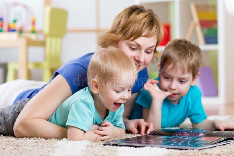 Madre y libro de lectura de los niños en casa foto de archivo
