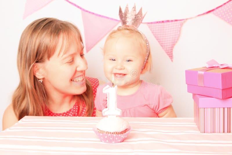 Madre y niña en la primera fiesta de cumpleaños fotografía de archivo