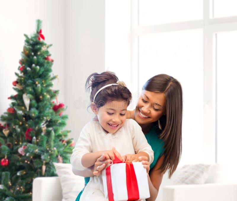 Madre y niña felices con la caja de regalo fotografía de archivo