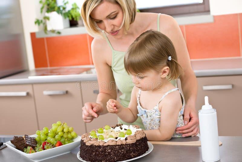 Madre y niño con la torta de chocolate en cocina imágenes de archivo libres de regalías