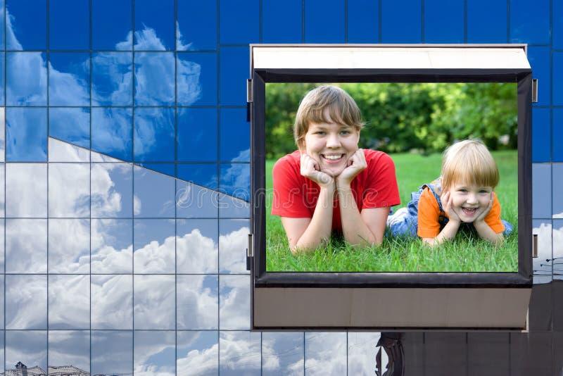 Madre y niño en el anuncio de la cartelera imagen de archivo