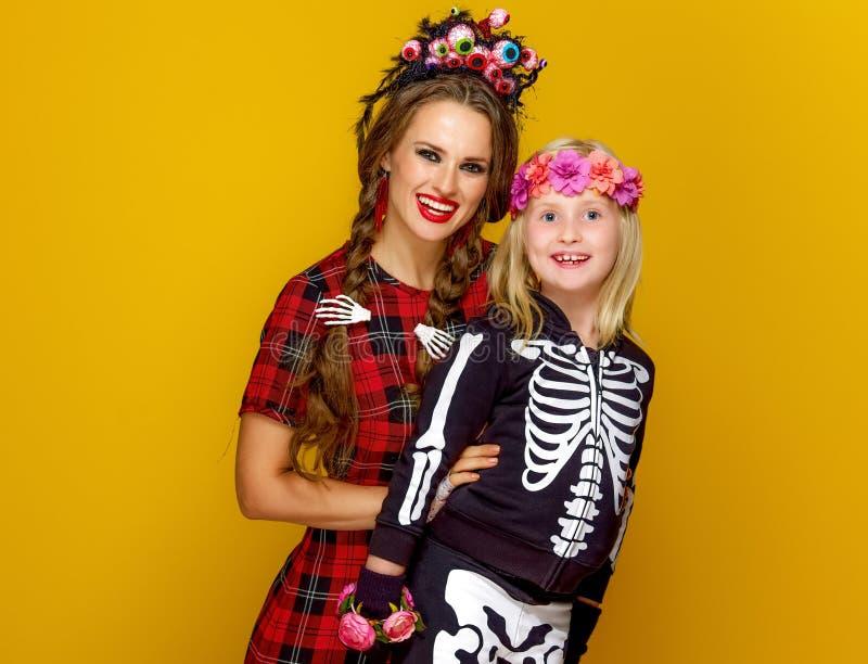 Madre y niño en el traje de Halloween en fondo amarillo imagen de archivo
