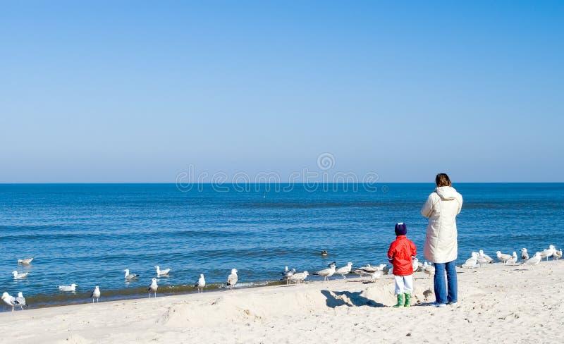 Madre y niño en la playa. imagen de archivo