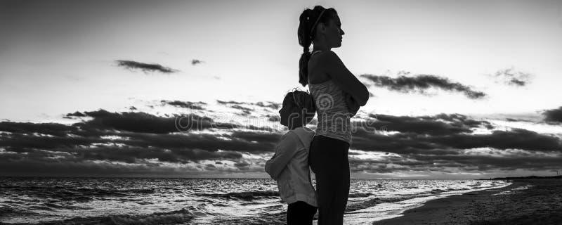 Madre y niño en la playa en la puesta del sol que se coloca de nuevo a la parte posterior fotos de archivo libres de regalías