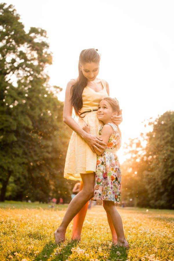 Madre y niño en la puesta del sol foto de archivo libre de regalías