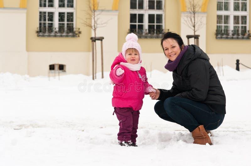 Madre y niño en nieve imagenes de archivo