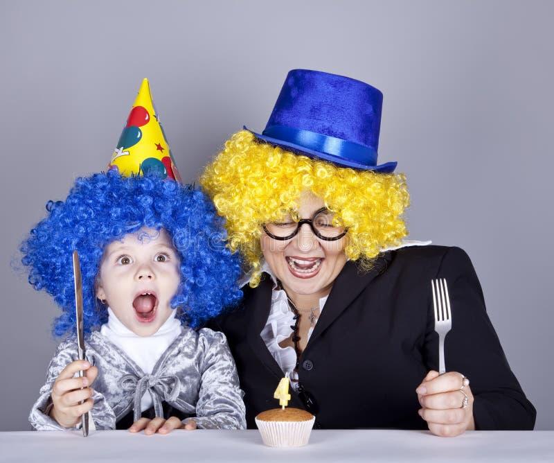 Madre y niño en pelucas y torta divertidas fotografía de archivo libre de regalías