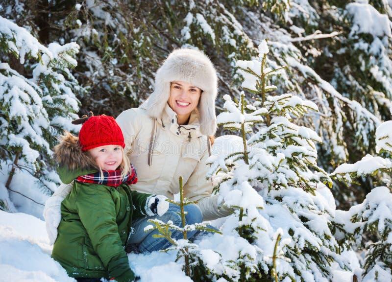 Madre y niño felices al aire libre entre piceas nevosas imagen de archivo
