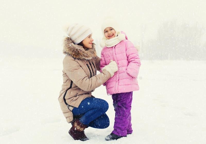 Madre y niño felices junto sobre los copos de nieve en invierno foto de archivo libre de regalías