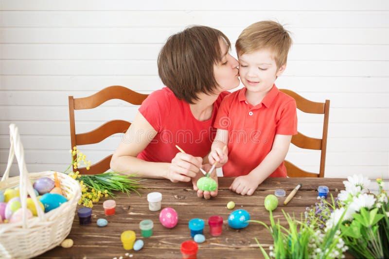 Madre y niño felices sonrientes que pintan los huevos de Pascua Huevos de Pascua felices de la pintura de la mamá de la familia y fotografía de archivo libre de regalías