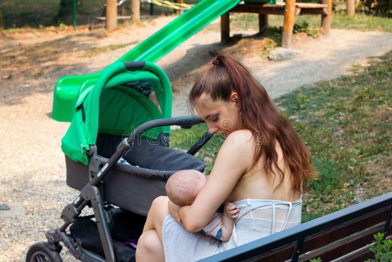 Madre y niño, hembra joven que amamanta a su bebé afuera, cuidando al bebé en sus brazos y alimentando con su leche del ` s de la foto de archivo