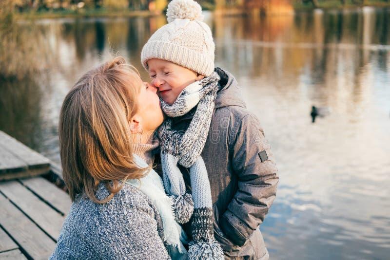 Madre y niño que abrazan en el parque del otoño cerca del lago Hijo feliz con la mamá que se divierte, relajación, disfrutando de imagen de archivo