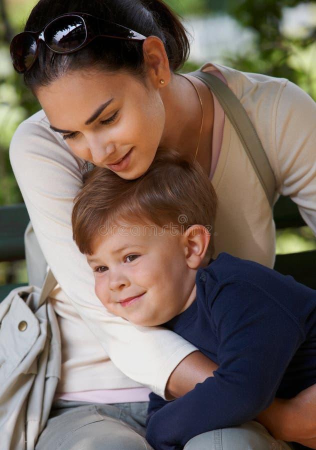 Madre y niño que abrazan en parque foto de archivo libre de regalías