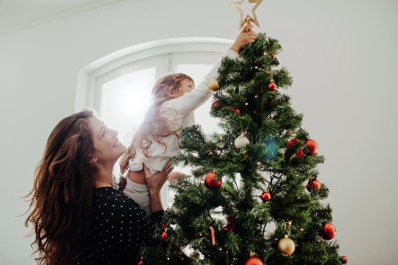Madre y niño que adornan el árbol de navidad imagenes de archivo