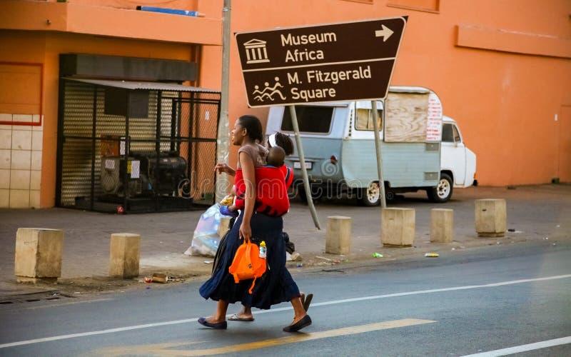 Madre y niño que cruzan una calle en Johannesburgo céntrico fotografía de archivo libre de regalías