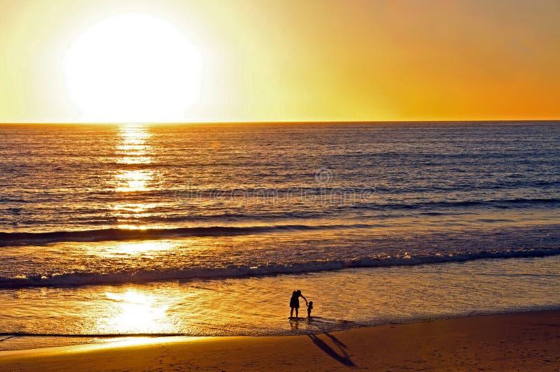 Madre y niño que juegan en la playa en la puesta del sol imagenes de archivo