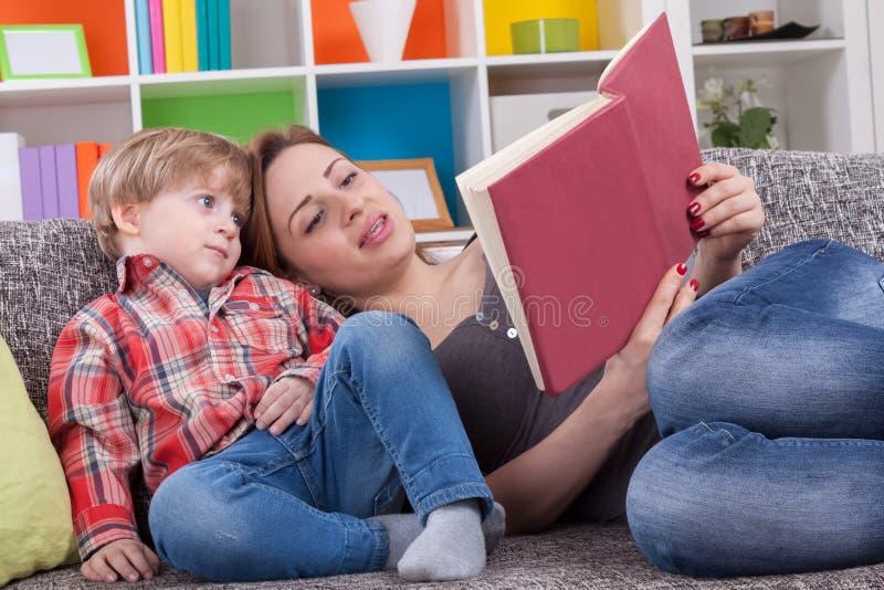 Madre y niño que leen un libro imagenes de archivo