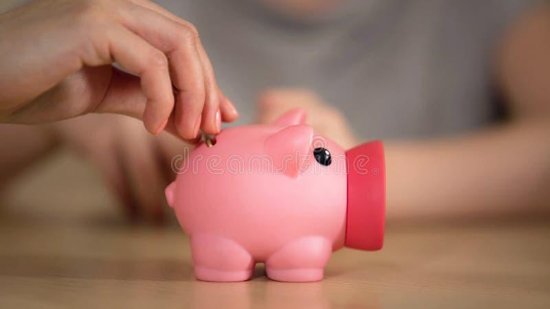 Madre y niño que ponen el dinero en la hucha, mamá que habla del presupuesto familiar foto de archivo