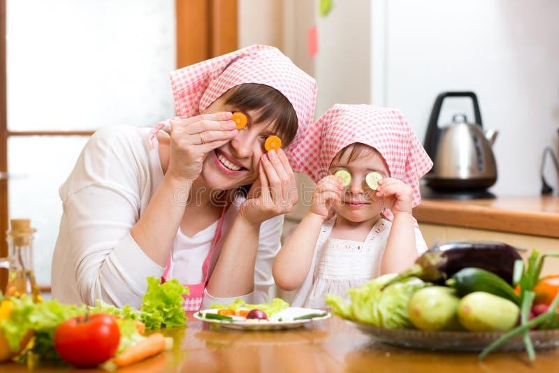 Madre y niño que preparan la comida sana y que se divierten foto de archivo libre de regalías